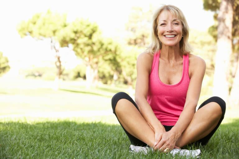 happy middle aged woman sitting on grass