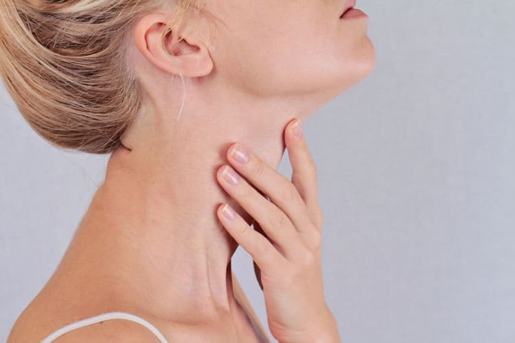 woman touching thyroid